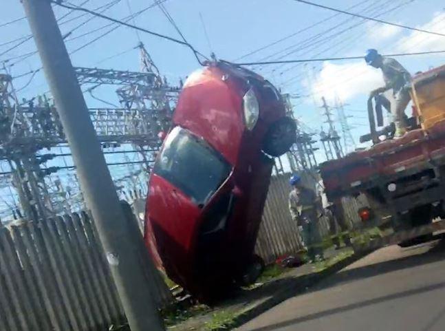 Vídeo: carro 'sobe' em poste e fica dependurado na fiação elétrica; assista!