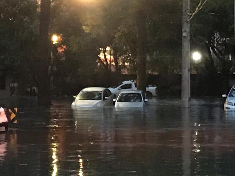 Carros parados ao lado do estádio Vila Capanema são arrastados por água após rio transbordar em Curitiba
