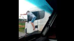 Vídeo: motorista dirige carreta com corpo para fora da janela e garrafa na mão