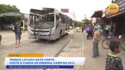 Ônibus lotado bate forte em poste e cabos de energia caem na rua