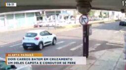 Dois carros batem em cruzamento, um deles capota e condutor se fere