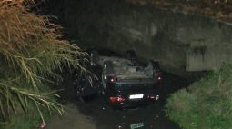 Motorista tenta desviar de carro de aplicativo e capota veículo dentro de córrego, em Curitiba